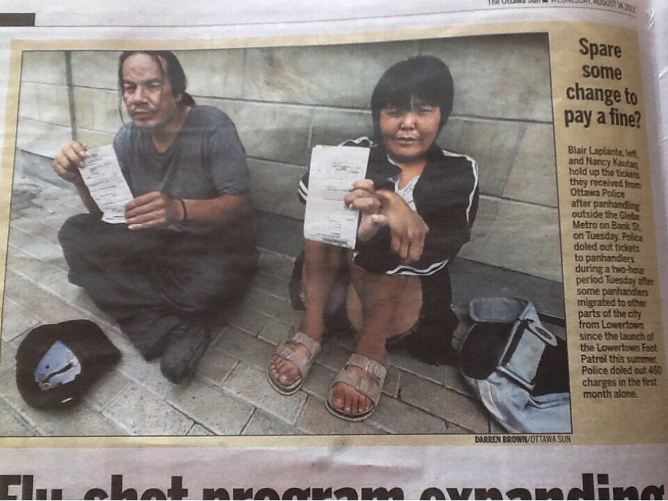 Two homeless on the sidewalk holding a fine they have been issued