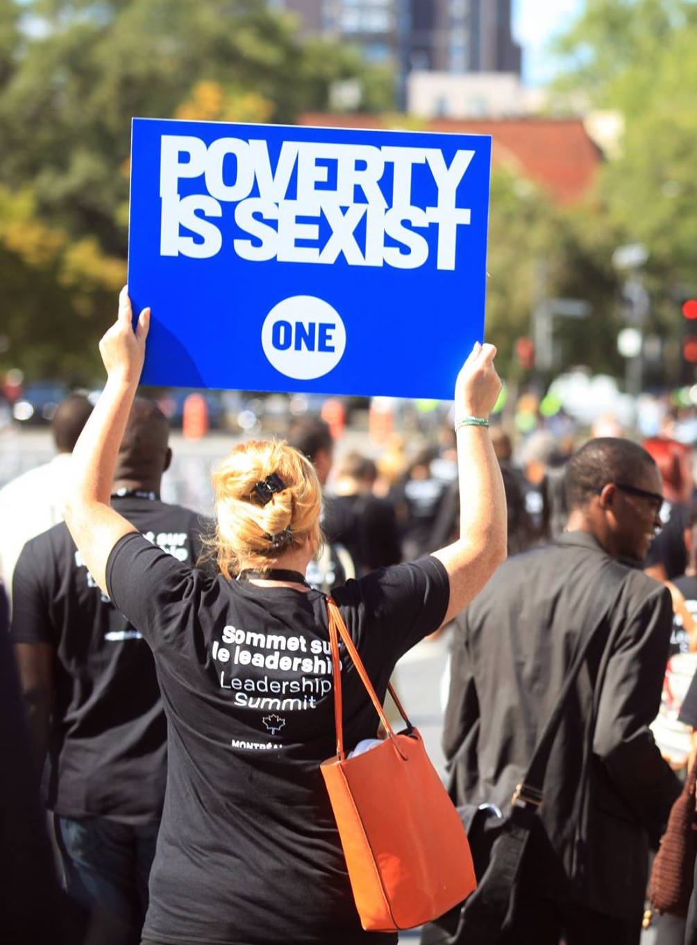 "A woman with a sign, ""Poverty is sexist."""